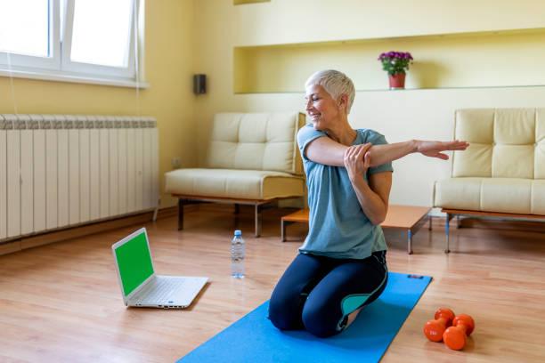 Femme aîné s'exerçant dans la gymnastique à la maison. - Photo