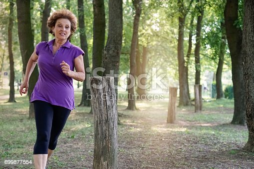 istock Senior woman exercising in the park 699877554