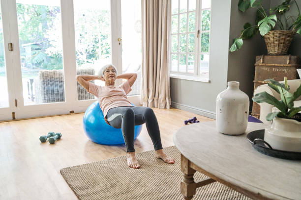 Senior woman exercising on a fitness ball at home stock photo