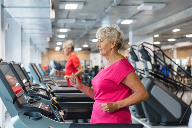 senior woman exercising on treadmill - runner rehab gym foto e immagini stock
