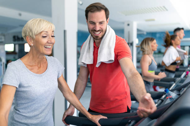 senior woman exercising on treadmill with coach standing by - runner rehab gym foto e immagini stock