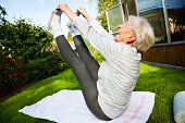 senior woman, 87 years old, very active and flexible, doing exercises in garden at a sunny summer morning