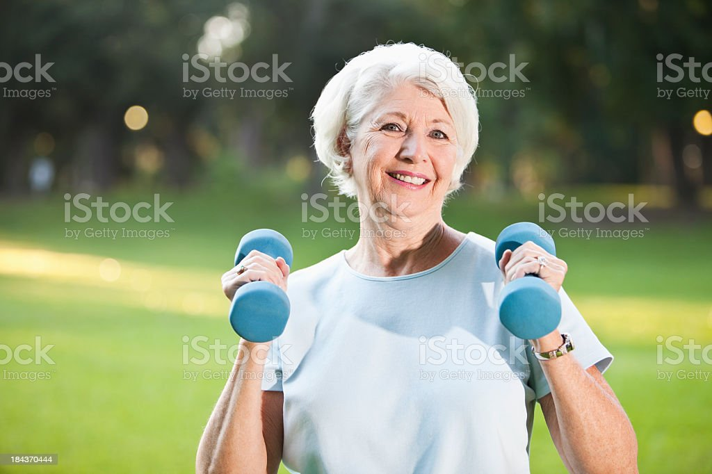 Senior woman exercising outdoors stock photo