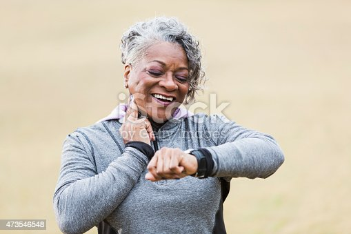 An African American senior woman, in her 60s, exercising outdoors in the park.  She is checking her pulse to see if her exercise has increased her heart rate.  She is smiling, with two fingers on her neck, looking at the watch on her wrist.  She is wearing a gray sweatshirt.