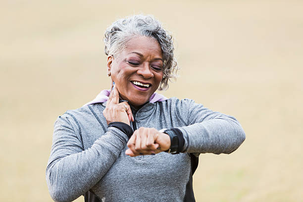 senior woman exercising, taking pulse - taking pulse stock photos and pictures