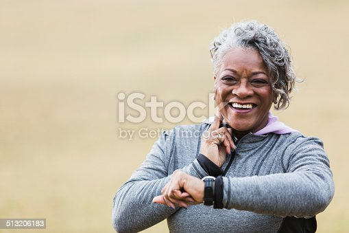African American senior woman (60s) exercising outdoors, taking pulse.