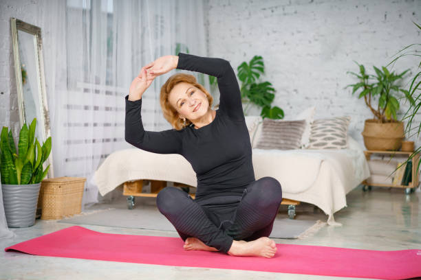 Senior woman exercising while sitting in lotus position. Active mature woman doing stretching exercise in living room at home. stock photo