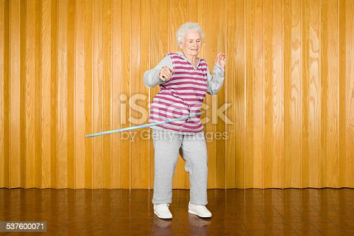 istock Senior woman exercising with a hula hoop 537600071