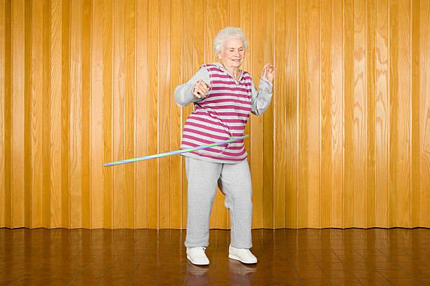 senior frau ausübung mit einem hula-hoop - hula hoop workout stock-fotos und bilder