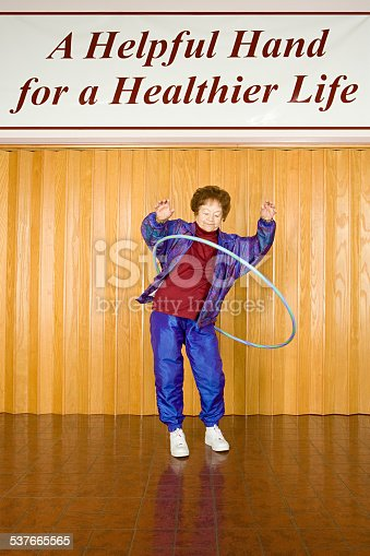 istock Senior woman exercising with a hula hoop 537665565