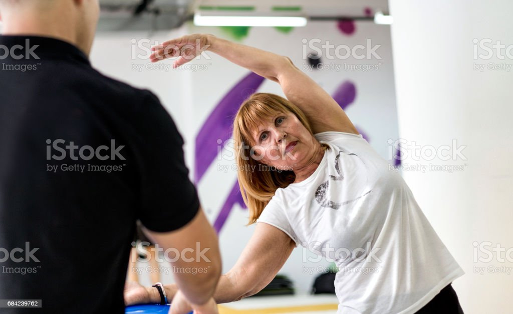 Senior woman exercising with instructor royalty-free stock photo