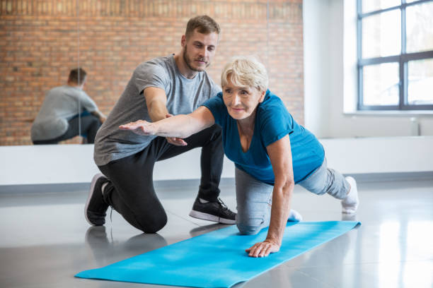 Senior woman exercising with trainer at rehab Senior woman being helped by her trainer in doing yoga workout at gym. Old woman with personal coach at rehab centre. drug rehab stock pictures, royalty-free photos & images