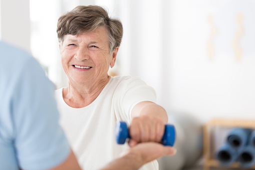 950649706 istock photo Senior woman exercising with weights 950649706