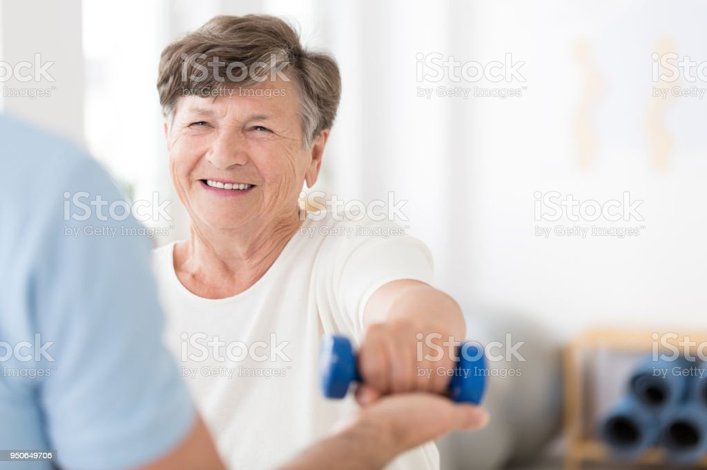 Senior woman exercising with weights stock photo