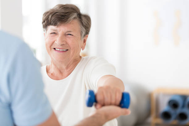 Senior woman exercising with weights Happy senior woman exercising arms with small weights with help from a physiotherapist and copy space recovery stock pictures, royalty-free photos & images