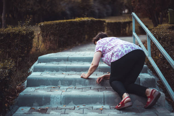 Senior woman fall on stairs outside stock photo