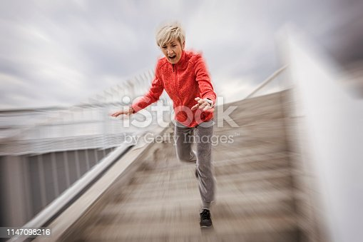 Senior woman falling down stone steps