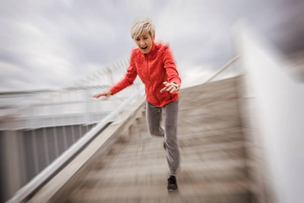 Senior woman falling down stone steps outdoors Senior woman falling down stone steps run down stock pictures, royalty-free photos & images
