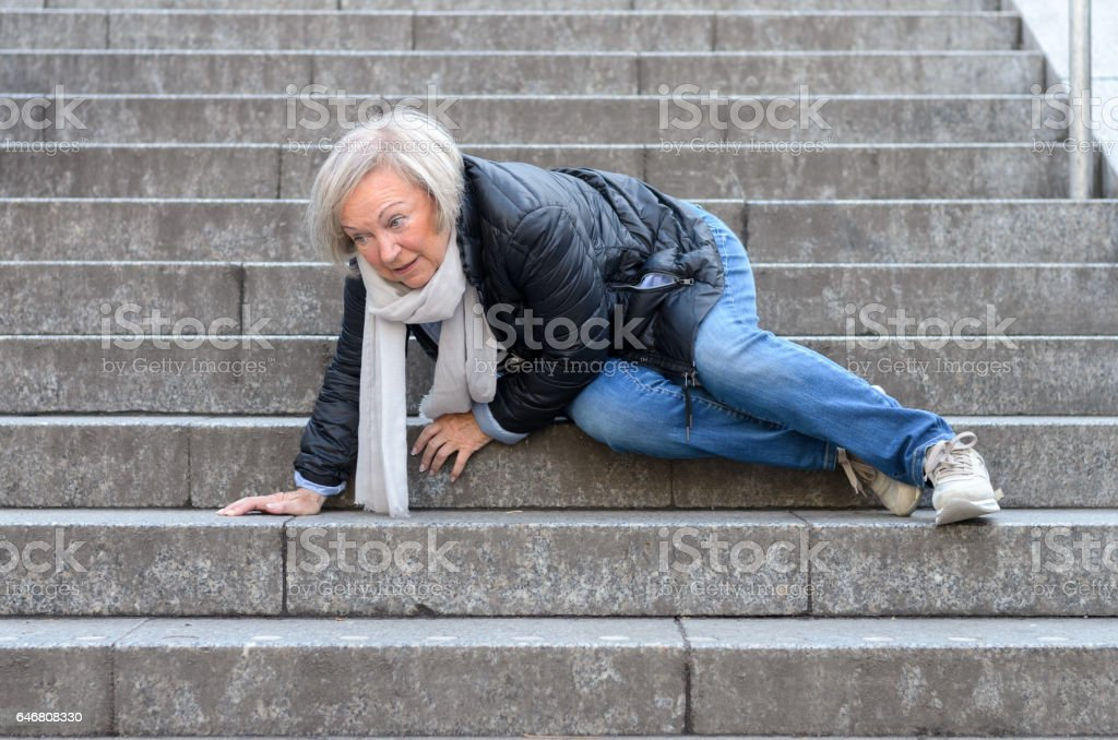 Senior woman falling down stone steps outdoors stock photo