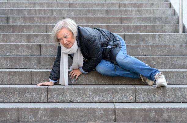 Senior woman falling down stone steps outdoors stock photo
