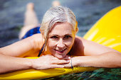 istock Senior woman floating on inflatable air mat in the sea 822793694