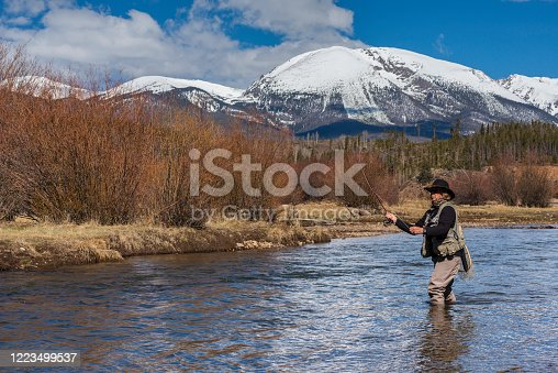 A senior woman fly-fishing in Lake Dillon, Colorado, near the towns of Frisco and Dillon in April.