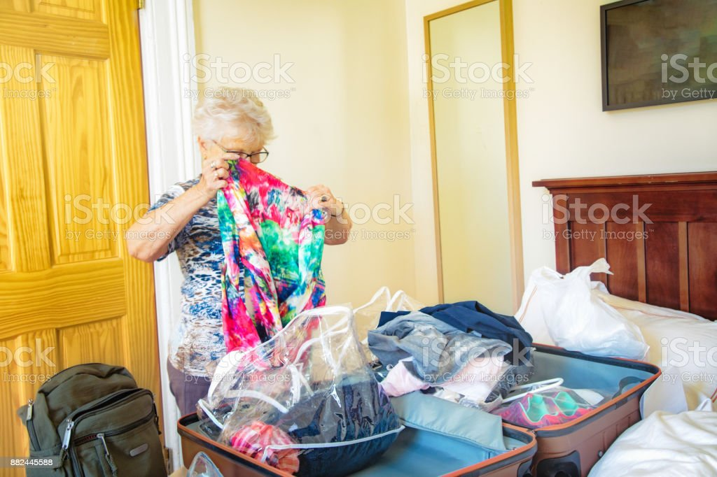 Senior woman folding clothes in a luggage using plastic bags stock photo