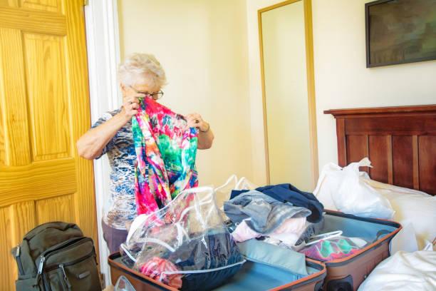 Ältere Frau Falten Kleidung in Plastiktüten mit Gepäck – Foto