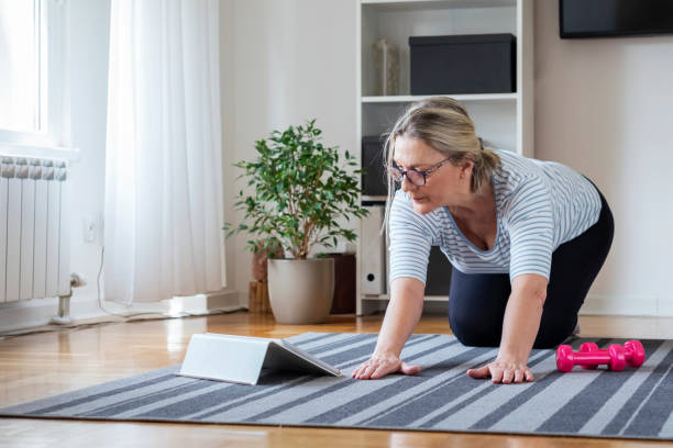 senior woman following tutorial online and exercise at home during isolation for covid - 19 at home - exercise at home stock pictures, royalty-free photos & images