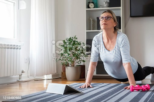 Senior woman following tutorial online and exercise at home during isolation for Covid - 19 at home.