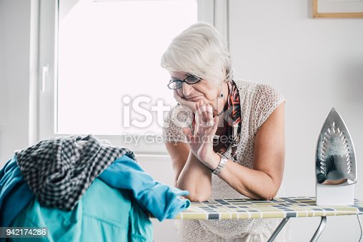 524159504 istock photo Senior woman frown at the laundry 942174286