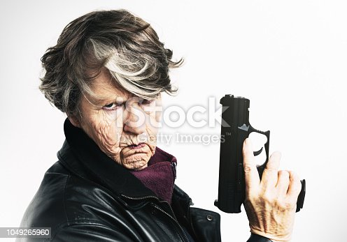 A wrinkled senior woman in a black leather jacket hold a semi-automatic pistol up, scowling and looking threatening.