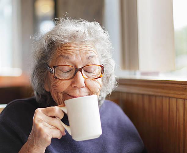 senior frau lustig gesicht lächeln mit kaffeetasse - gesichtertassen stock-fotos und bilder