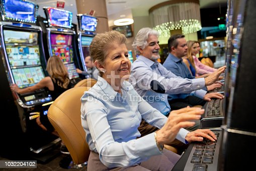 Senior woman gambling on slot machine looking very happy and other people gambling also at the background