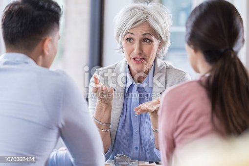 A young couple sit at a table across from a senior counselor. The female, counselor gestures to them as she talks.