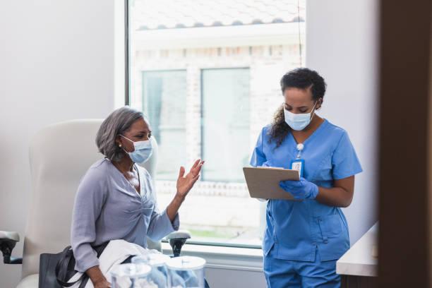 Senior woman gestures while talking with nurse stock photo