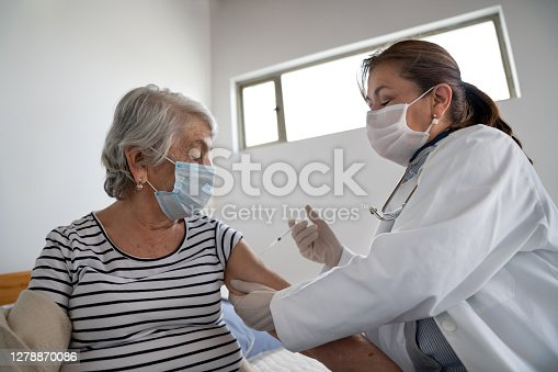 Latin American senior woman getting a COVID-19 vaccine by a doctor at a nursing home – illness prevention concepts