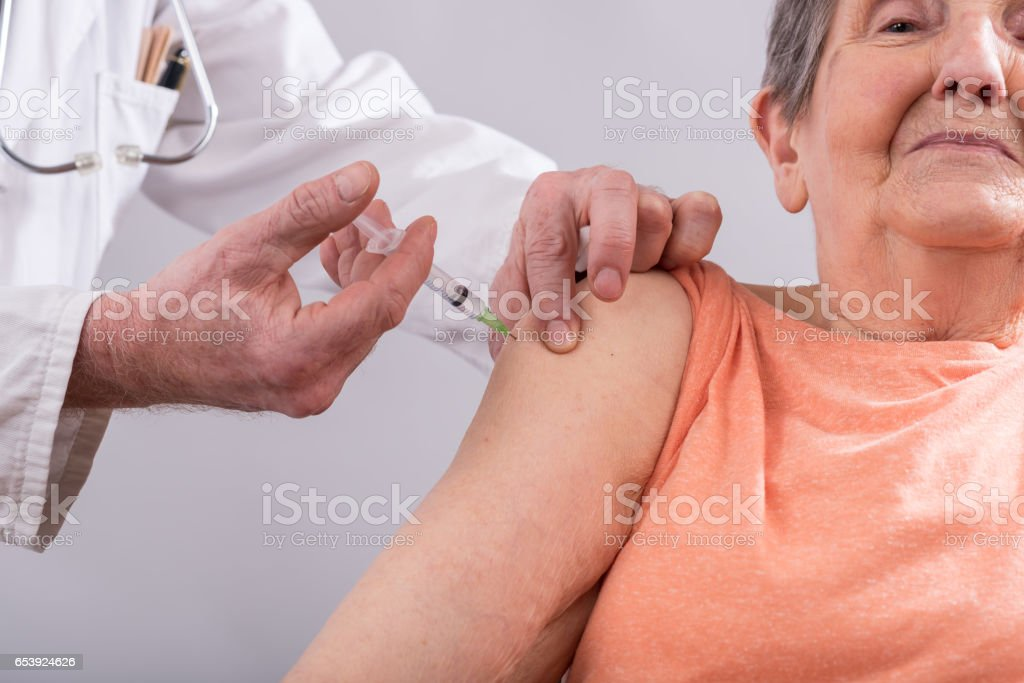 Senior woman getting an injection stock photo
