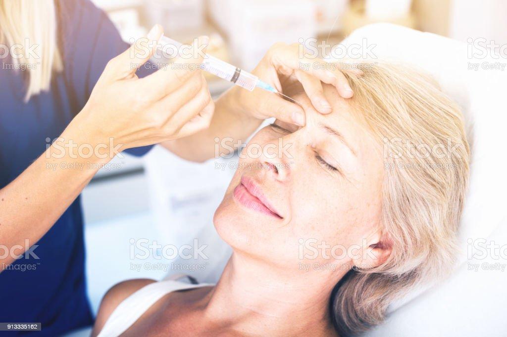Senior mujer conseguir inyección facial - foto de stock