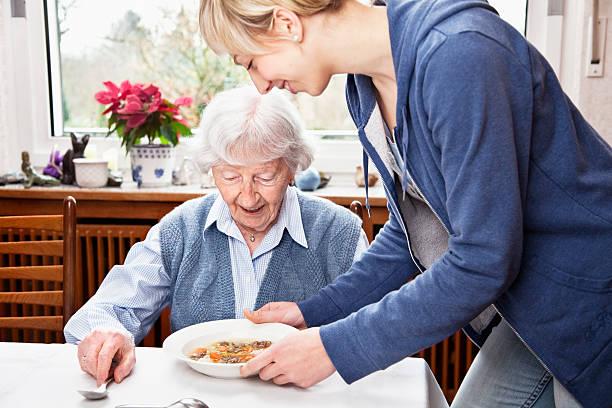 senior Frau immer Suppe serviert von der fürsorgliche – Foto