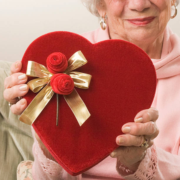 senior woman gives a heart shaped valentine's day gift - senior valentine stock photos and pictures