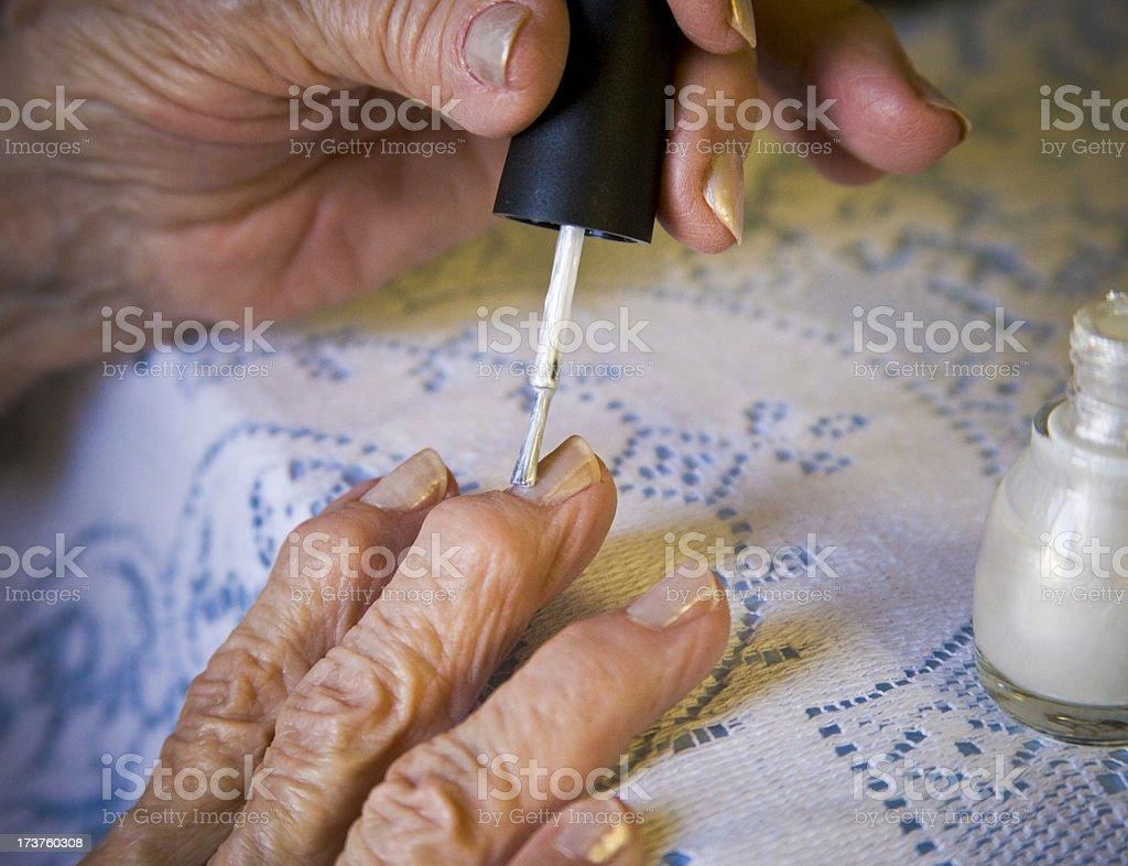 senior woman gives herself a nail polish manicure royalty-free stock photo