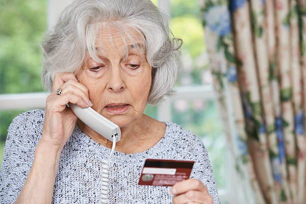 Senior mujer que la información de la tarjeta de crédito en el teléfono - foto de stock