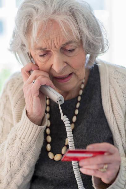 senior femme, donnant les détails de votre carte de crédit sur le téléphone - seulement des femmes seniors photos et images de collection