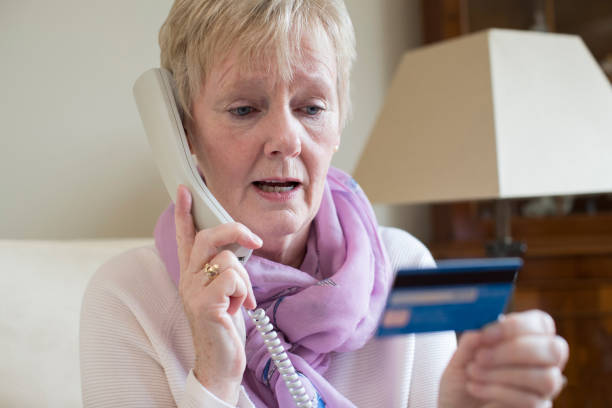 Senior Woman Giving Credit Card Details On The Phone Senior Woman Giving Credit Card Details On The Phone phone charging stock pictures, royalty-free photos & images