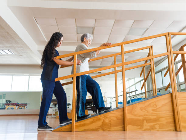 Senior woman going up a ramp during physical therapist stock photo
