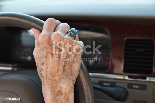 Senior woman driving car. Hand with ring on steering wheel.