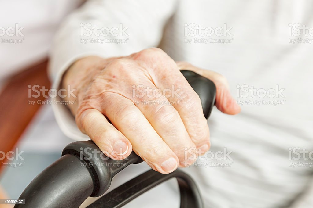 senior woman hands grabbing grip of walker stock photo