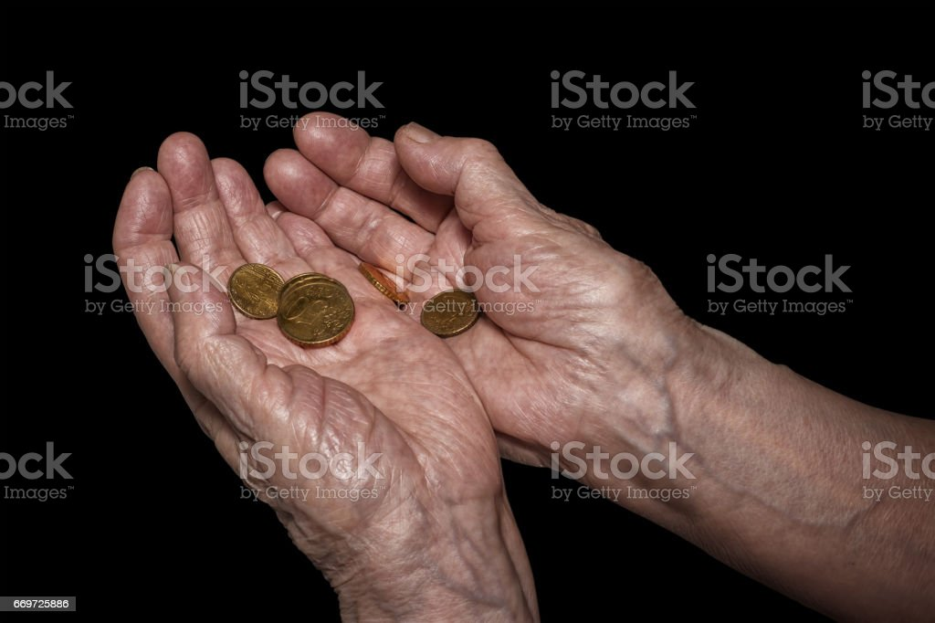 Senior woman hands holding some euro coins. Pension, poverty, social problems and senility theme. stock photo