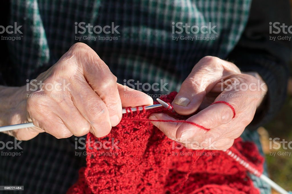 Senior woman hands knitting with red wool foto royalty-free